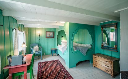 Green bedroom with enclosed bed and green walls.