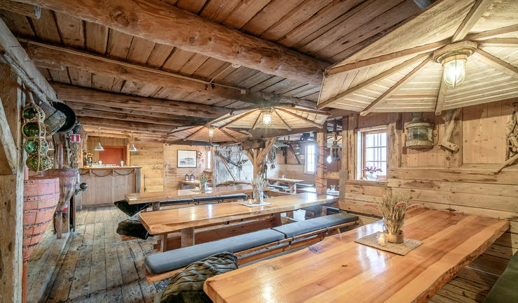 Inside of wooden cabin with long wooden dining tables