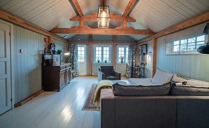 Large pale blue room with wooden floors suite