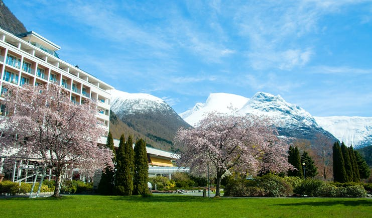 Hotel Alexandra Loen modern hotel with balconies and blossom on trees with snow on mountain tops behind