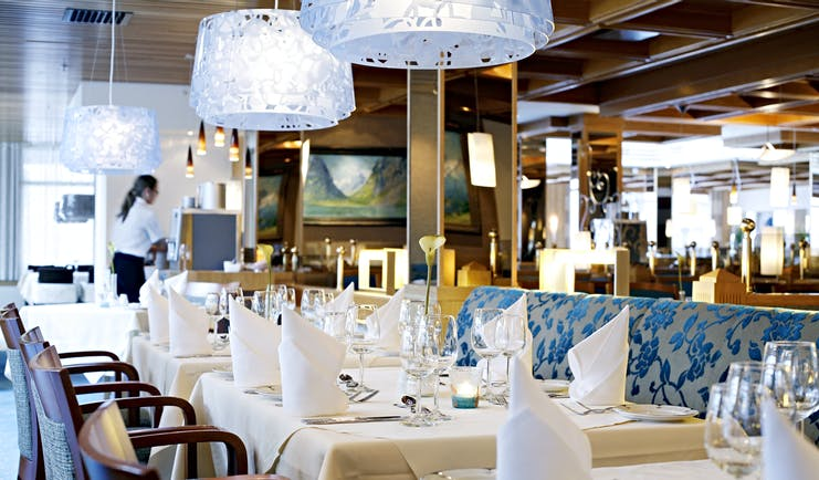 Hotel Alexandra Loen blue chairs of restaurant with large glass lights