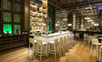 Bar with white high chairs and wooden floor at Bergen Bors
