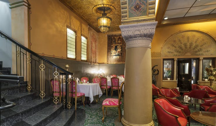 Traditional bar and restaurant with stairs and pillar and red chairs at the Hotel Bristol oslo