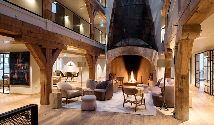 Hotel Brosundet Alesund lobby with large fireplace and galleries above