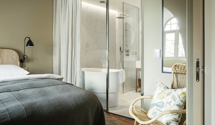 Hotel Brosundet Alesund bedroom with grey covers and glass bathroom window