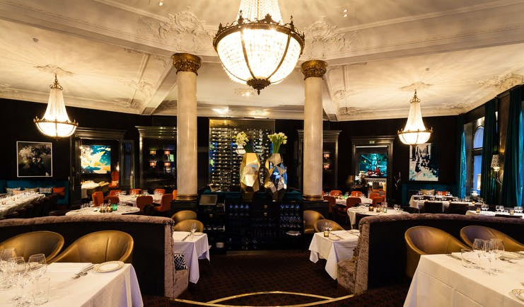Hotel Continental Oslo restaurant with dark floor and large white chandeliers