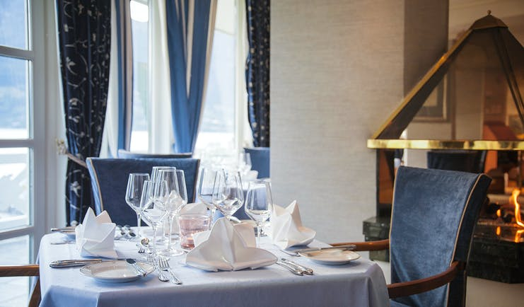 Hotel Ullensvang Norway table with blue tablecloth and open fire behind