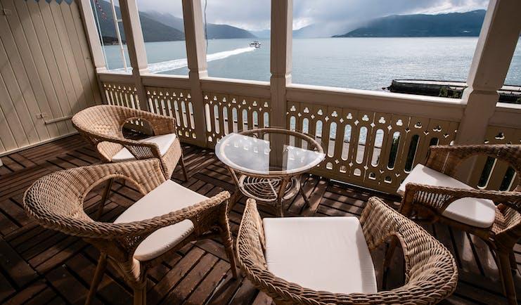 Four wicker seats on balcony overlooking fjord at Kviknes Hotel