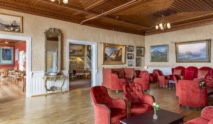 Red armchairs in lounge with wooden floor Kviknes