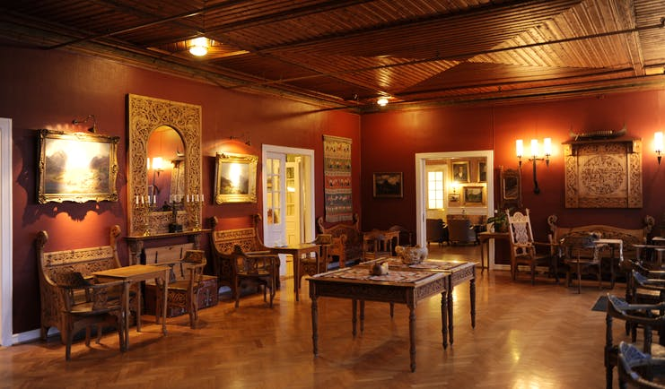 Dark wooden room with lights on walls and antique rustic furniture at Kviknes hotel