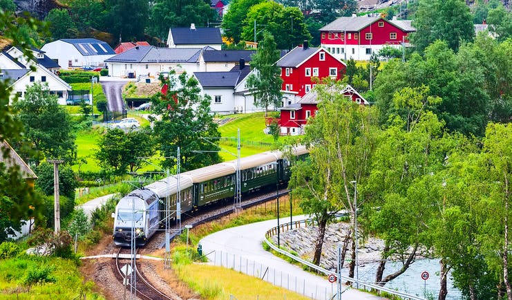 Train in country with red houses Flam to Myrdal