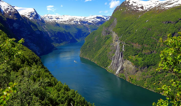 Fjord in Norway with snow capped mountains on each side