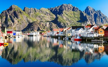 Fishing village by water with mountains behind Henningsvaer Lofoten