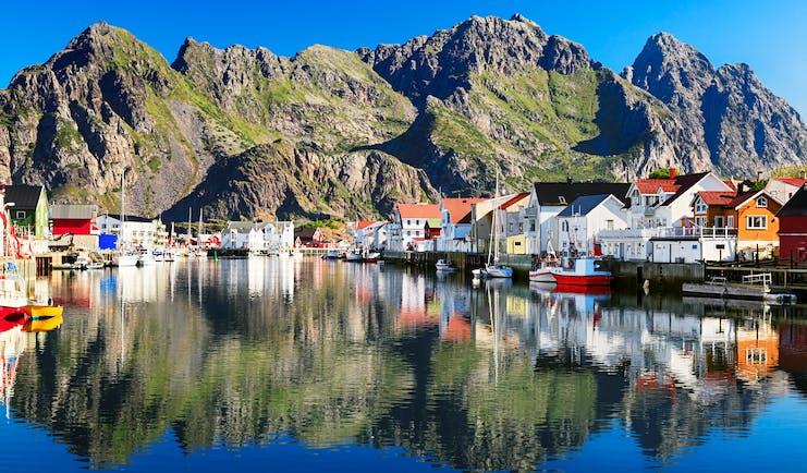 Fishing village by water with mountains behind Henningsvaer Lofoten