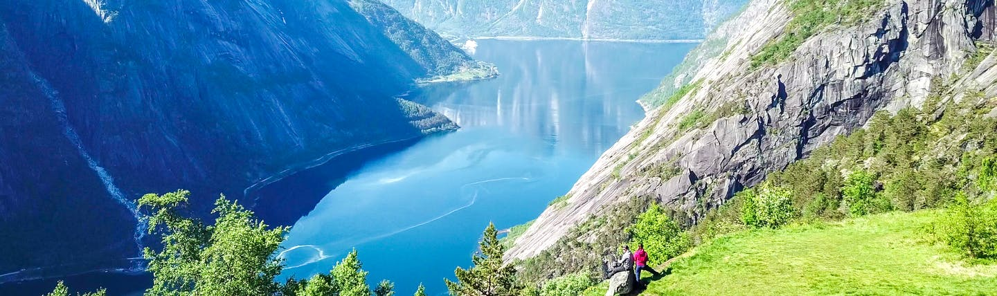 Couple overlooking the Eidfjord with steep cliffs and deep blue waters
