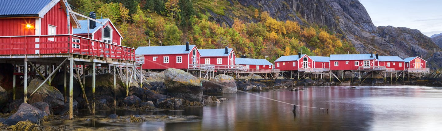 Red wooden houses on stilts over water at Nusfjord Lofoten