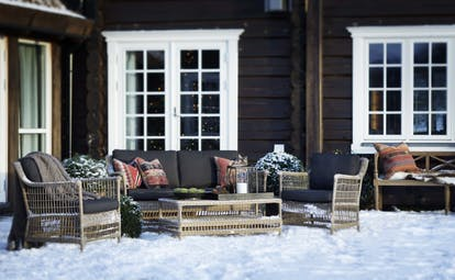 Storfjord Hotel patio with snow on ground and seating