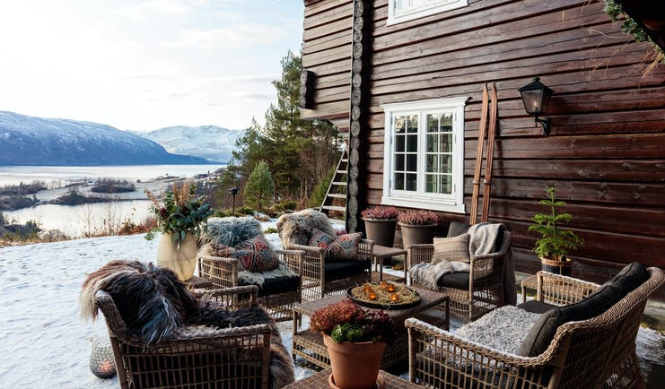 Storfjord Hotel patio with armchairs outside dark wooden house