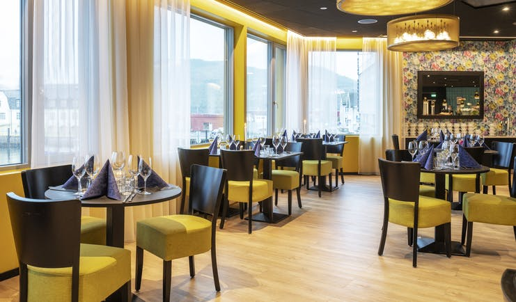 Thon Hotel Harstad restaurant with brown tables and yellow seats to chairs