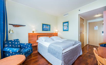 Thon Hotel Harstad bedroom with wooden floor, blue chair and white ad grey bed coverings