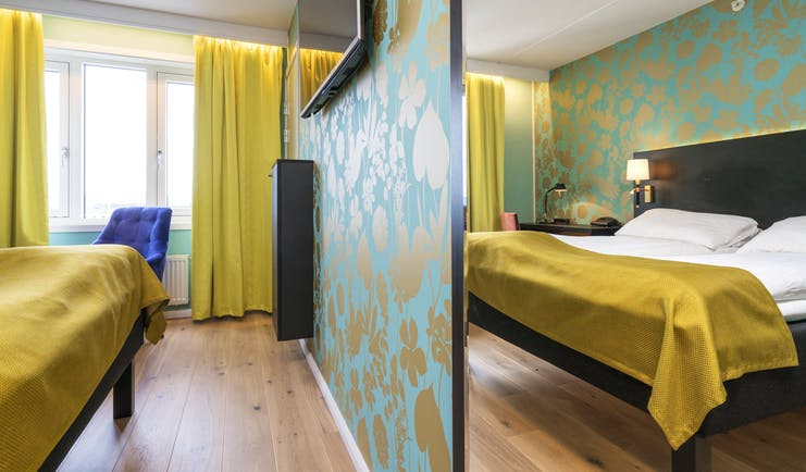 Thon Hotel Nidaros room with wooden floor, yellow curtains and bedspread and green patterned walls