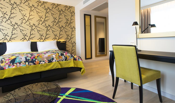 Rooom with wooden floor and colourful bedspread Thon Hotel Rosenkrantz Oslo