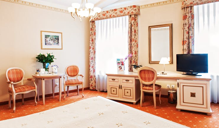 Bedroom with dressing table, television, a chandelier and curtains