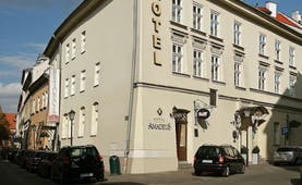 White plastered exterior of two storey hotel on corner of road Hotel Amadeus Krakow