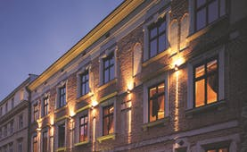 Hotel Copernicus Krakow exterior stone building with large windows and an arched entrance
