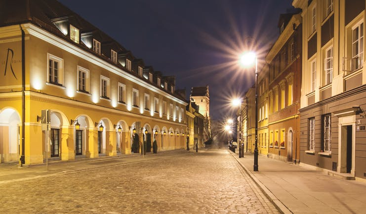 Mamaison Le Regina Warsaw exterior yellow building with archways and lamps on a cobbled street