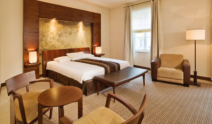 Mamaison Le Regina Warsaw superior bedroom  wooden headboard and painting of vines table and chairs