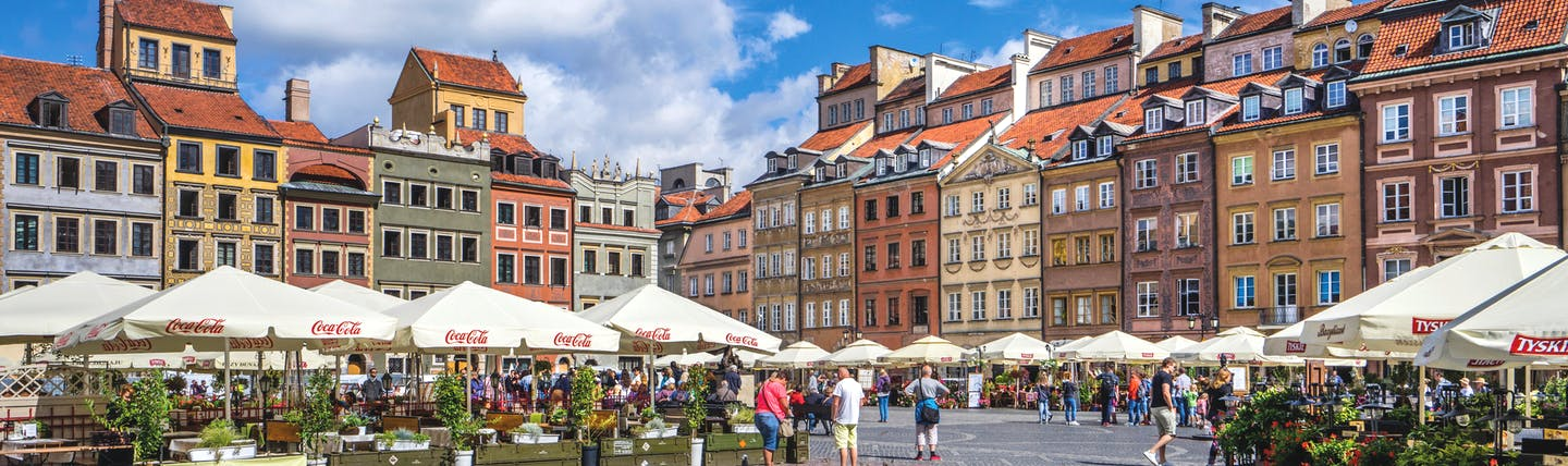 Baroque coloured buildings around square with white awnings over market stalls in Warsaw