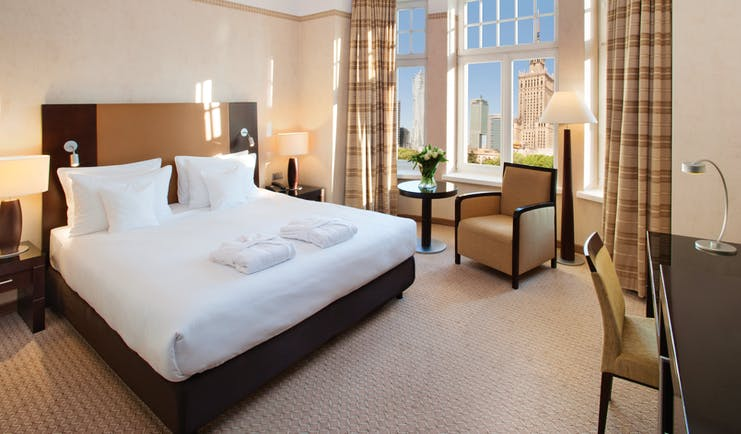 Polonia Palace Hotel deluxe rom with large windows looking over the city, a double bed, a desk and brown and beige colour scheme