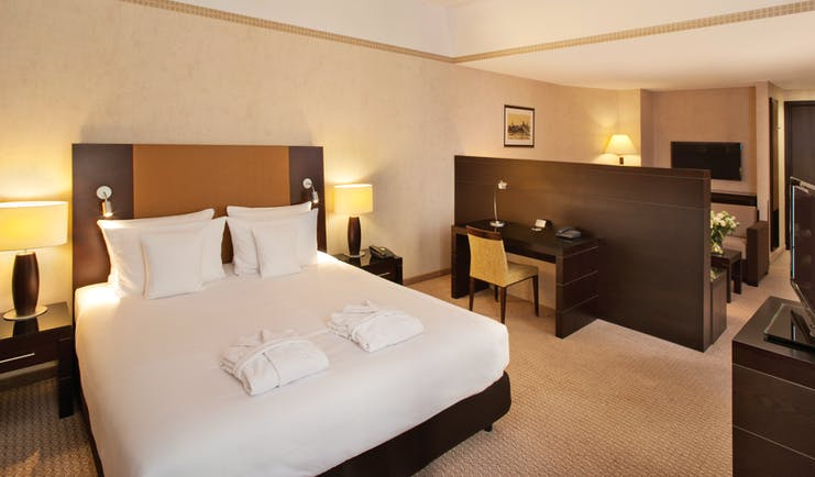 Polonia Palace Hotel junior suite with double bed, desk, television and brown and beige colour scheme