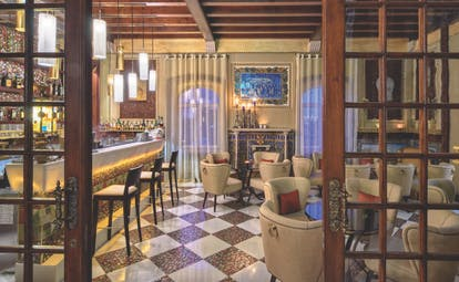 View of the Bela Vista Hotel & Spa with wooden ceilings, tiled floors, wooden high bar chairs and beige coloured arm chairs for seating