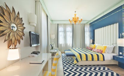 View of the Bela Vita Hotel & Spa Character room with a double bed and television decorated in yellow and navy