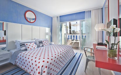 Deluxe room at the Bela Vista Hotel & Spa, decorated in blue and red with double doors leading out to a private patio area