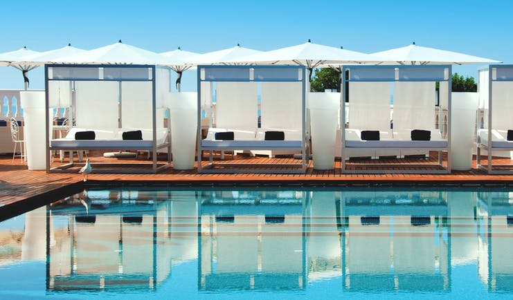 View of the clear blue pool at Bela Vista Hotel & Spa with cabana sunbeds shown reflecting in the water