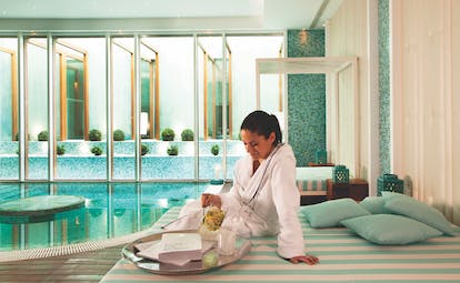 Woman on lounge area drinking lemon water next to plunge pool in spa area of Bela Vista Hotel and Spa