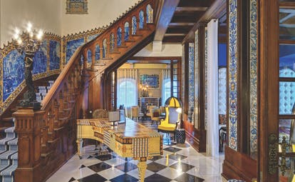 large wooden staircase leading upstairs with blue painting on the walls next to a yellow and blue patterned piano on the ground floor