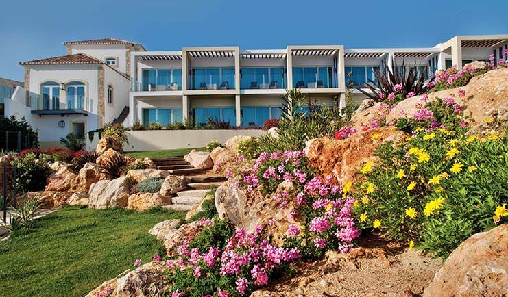 View of the Bela Vista Hotel & Spa from the gardens, displaying green grass and pink and yellow flowers