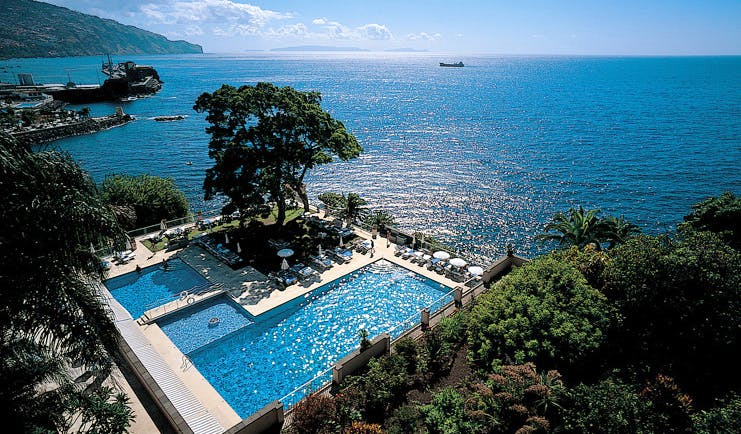 Belmond Reid's Palace Portugal aerial outdoor pool trees loungers umbrellas sea view