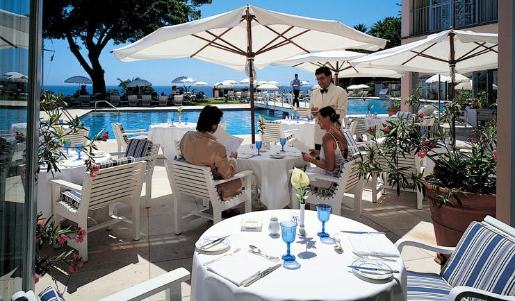 Belmond Reid's Palace Portugal restaurant indoor and outdoor dining area umbrellas pool view