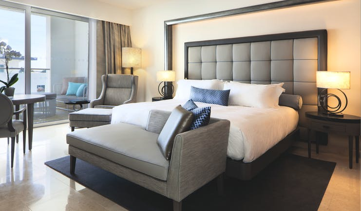 Conrad Algarve deluxe room, bed armchair, bright modern decor, balcony