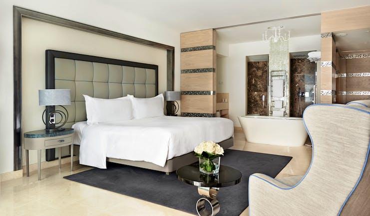 Conrad Algarve grand deluxe room, large bed, armchair, bath, comfortable modern decor