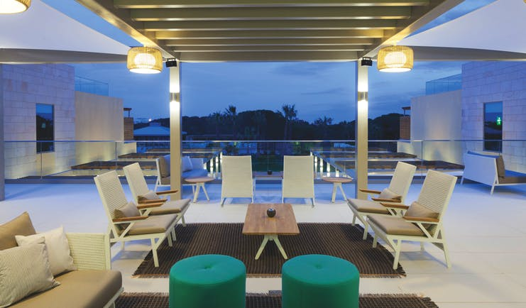 Epic Sana terrace bar on hotel roof, modern chairs and green footstools