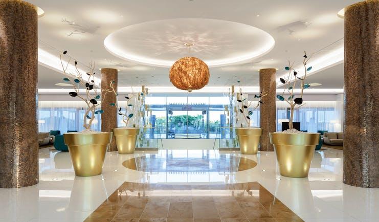 Epic Sana lobby, modern decor, marble floors and columns, colourful flower sculptures