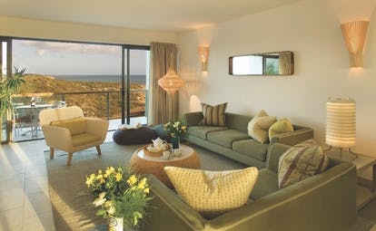 View of a bay house standard room looking over rocks and the sea with big grey sofas and flowering decorating the room