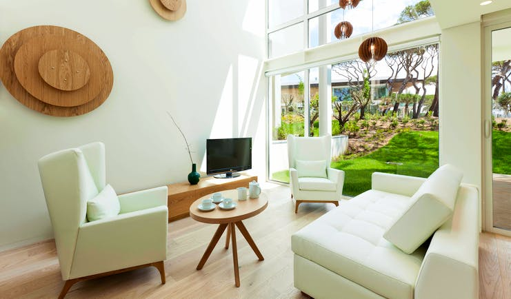 Martinhal Cascais Portugal luxury villa lounge with armchairs and floor to ceiling windows overlooking garden