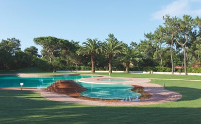 Martinhal Cascais Portugal outdoor pool in lawned area with palm trees